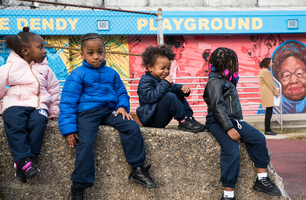 Neighborhood children watch from afar as a mural is dedicated at Marie Dendy Playground in North Philadelphia on October 24, 2018. Brianna Spause / Philadelphia Parks & Recreation
