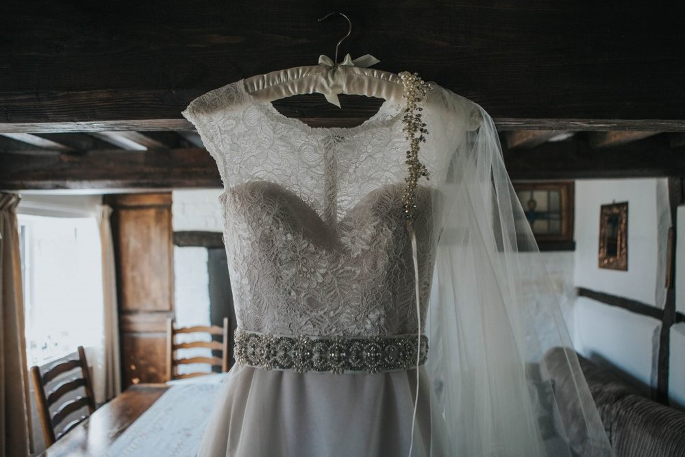 A wedding dress hanging on a coathanger.jpg