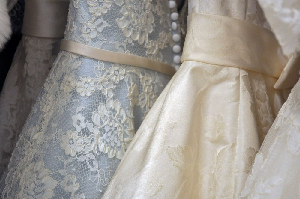 Three wedding dresses hanging on a rack.jpg