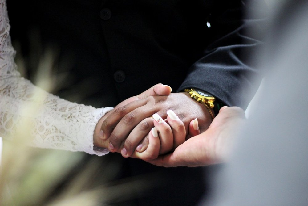 A couple hold hands as they say their wedding vows.jpg