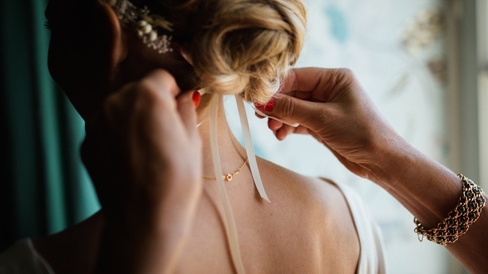 A bridesmaid tying her bride's hair before the ceremony.jpg