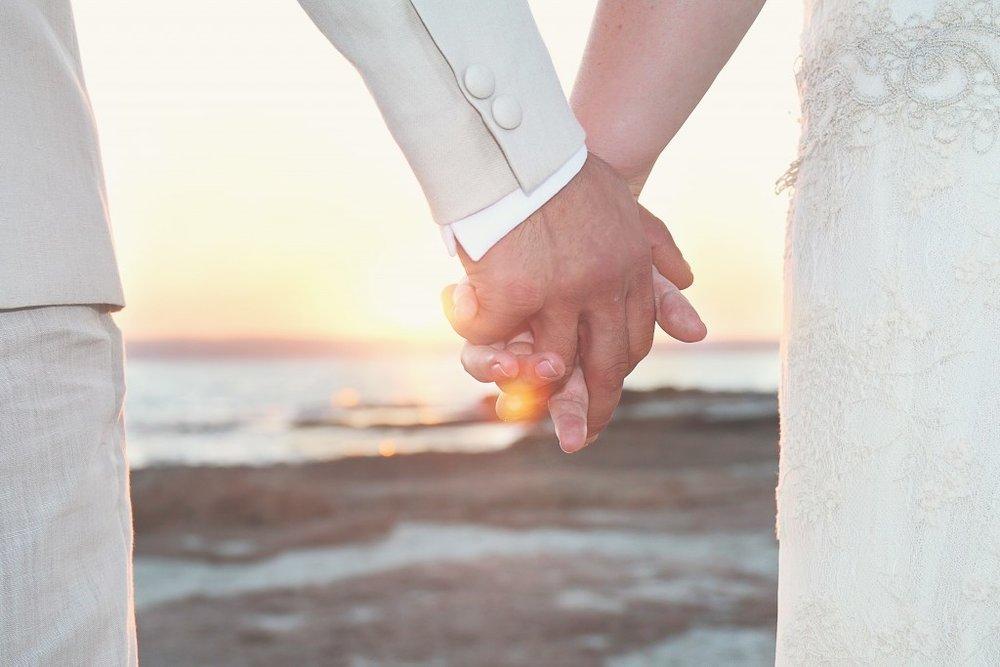 A couple hold hands on the beach.jpg