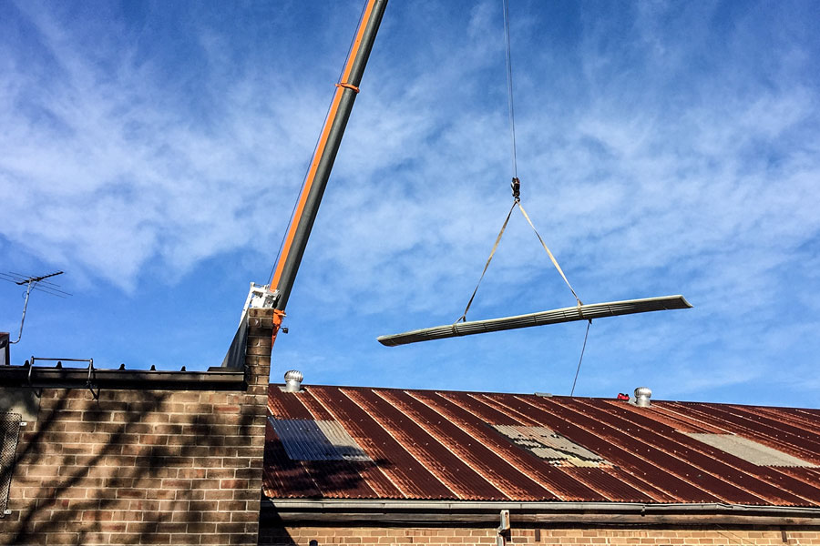 Crane lifting a beam over a warehouse renovation