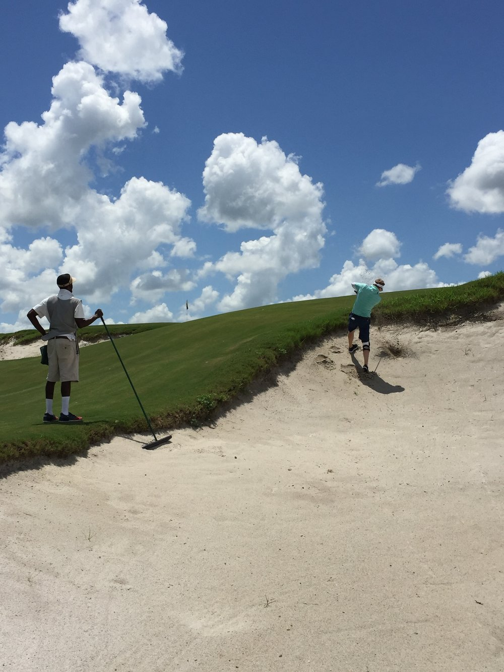 Cameron, my fiancé, tears his way out of a steep bunker on Blue with our trusty caddie Nick watching.