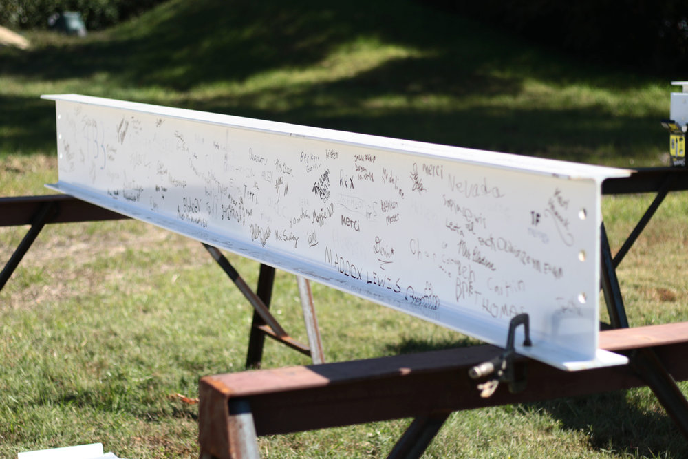 All School Beam signing - October 22, 2018 - Walden students, faculty and staff, and Capital Campaign donors were invited to leave their mark for the commemoration of the buildings set to open their doors in early 2019. Two of the beams were painted white and by the end of the week, a complex mosaic of black Sharpie signatures lay resplendent across their surfaces.