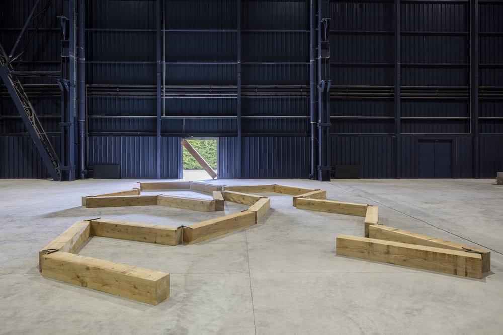 Contorted Positioning , 1982/2016 曲位 ( Kyokui ) Wood, twigs 27 x 1000 x 800 cm Installation view, Kishio Suga: Situations , Pirelli HangarBicocca, Milan, 2016 Photo: Agostino Osio; Courtesy Pirelli HangarBicocca, Milan