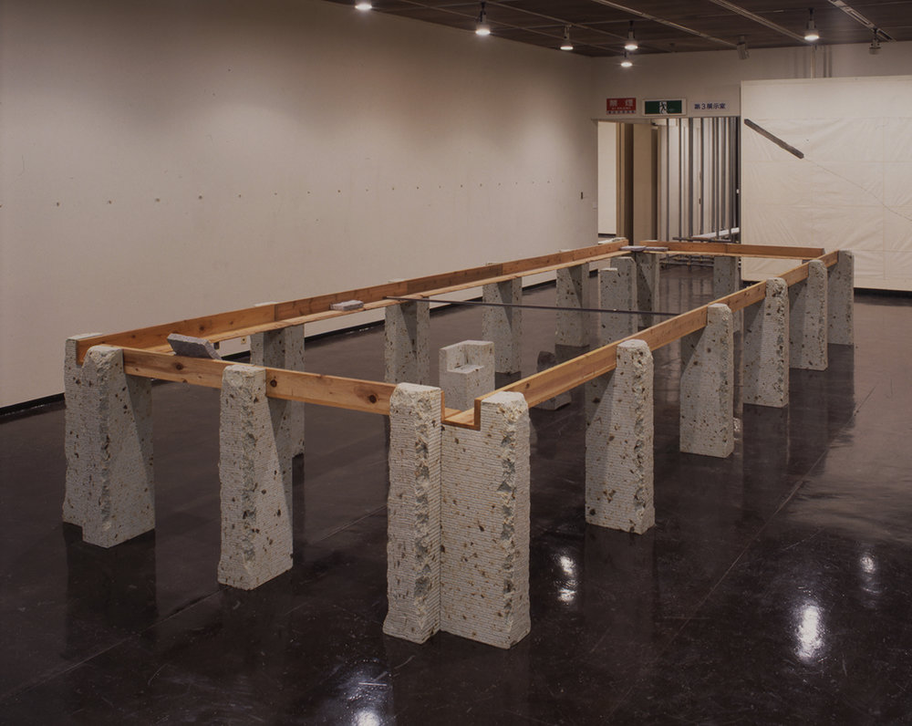 Supported Surrounding , 1987 縁辺仕帯 ( Enpen Shitai )  Wood planks, stone, aluminum 41 3/8 x 103 3/4 x 305 1/2 inches overall Installation view,  Kishio Suga , Kanagawa Prefectural Gallery, Yokohama, 1998 Courtesy Kanagawa Prefectural Gallery, Yokohama