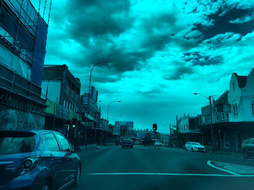 Alt-Text: Sydney, Australia street with buildings to left and right and cars in street with teal filter.