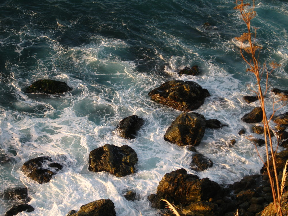 Alt-Text: over-cliff view of ocean foam around rocks in Big Sur sea at sunrise.