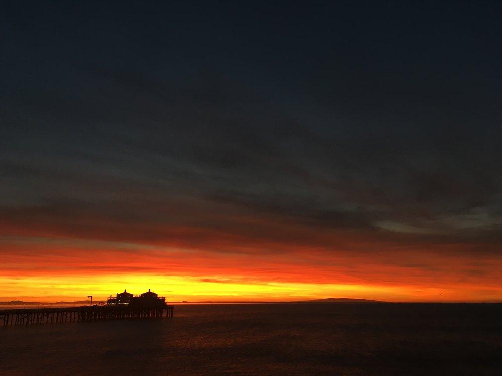 Alt-Text: sunrise over lifeguard station on beach