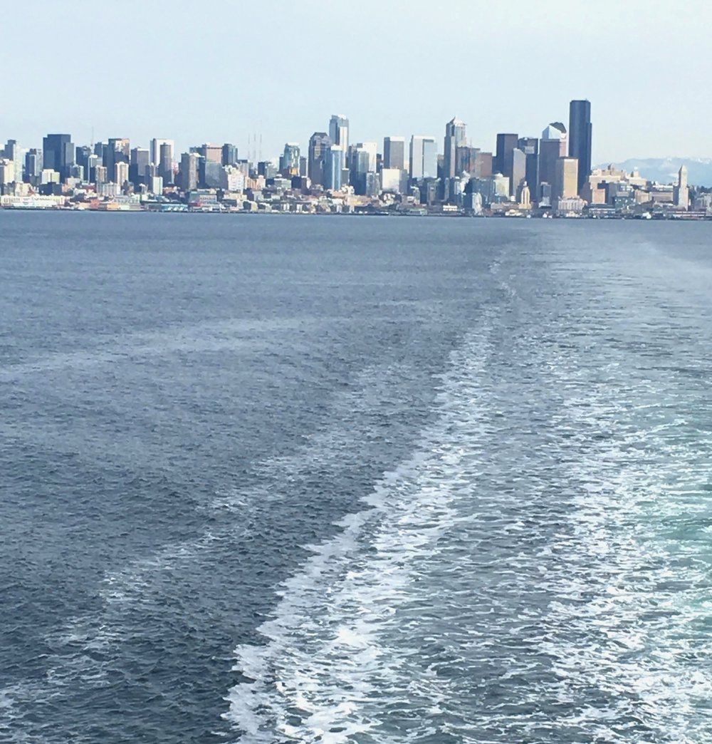 Si'ahl (Seattle) downtown skyline in background, wake from ferry in foreground, daytime.