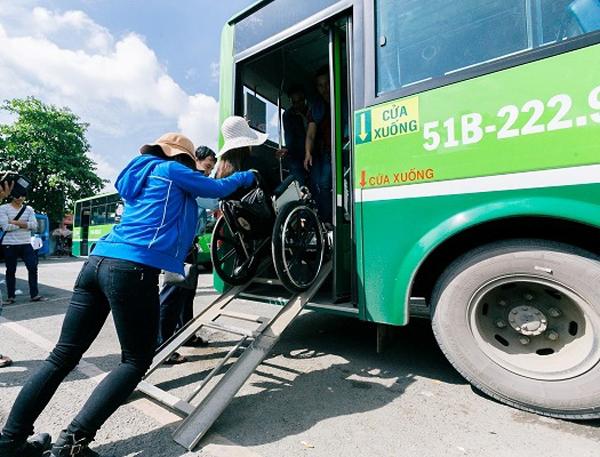 Tiếp viên xe buýt đẩy xe lăn hỗ trợ người khuyết tật