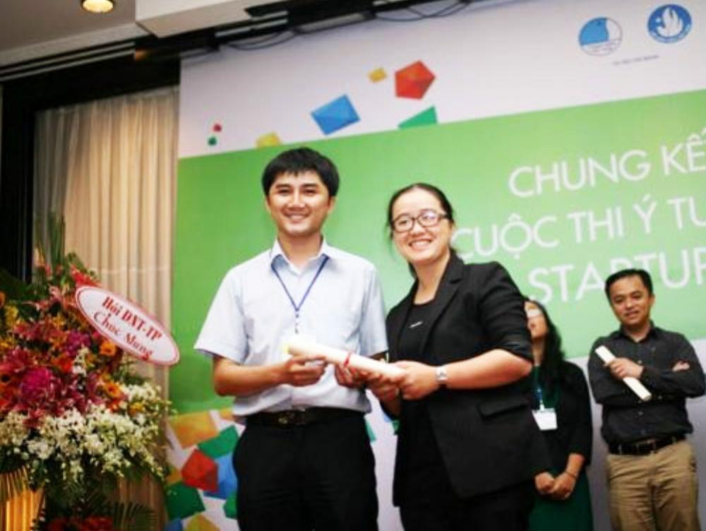 Anh Đỗ Hữu Tân (trái)đang nhận phần thưởng từ chị Nguyễn Thị Diệu Hằng (phải)trong một chương trình hỗ trợ khởi nghiệp. (Ảnh: Magix)