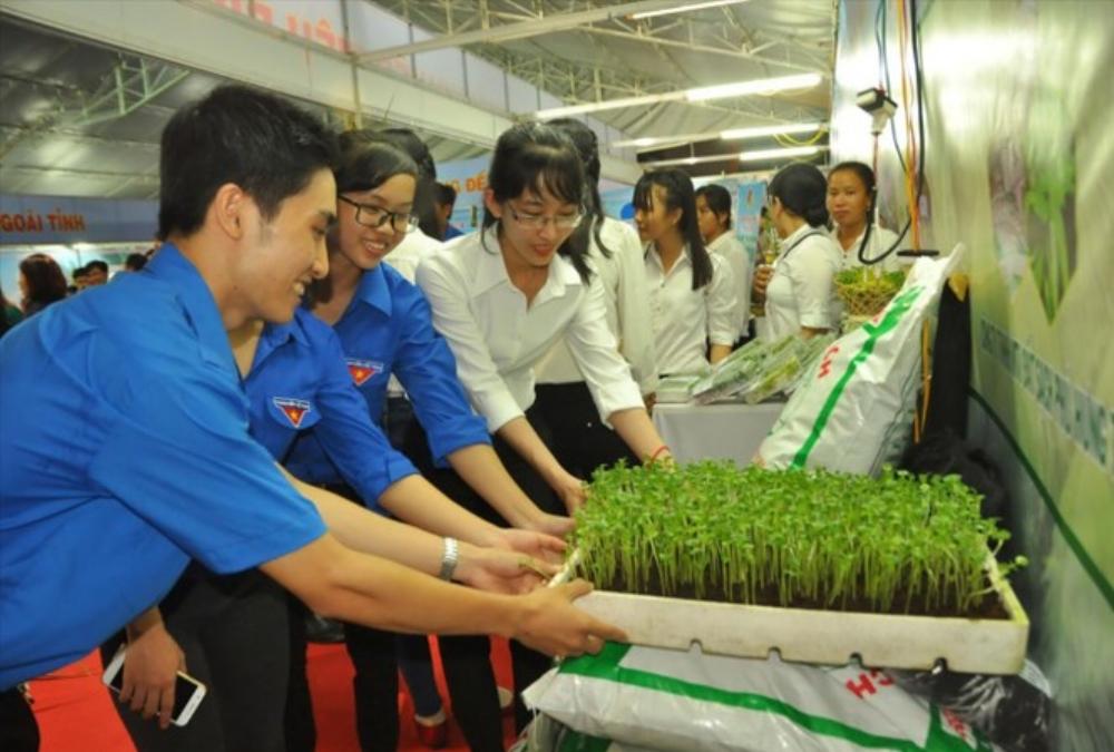 Phan Gia Thịnh (bên trái) với sản phẩm rau mầm trồng bằng đất sạch do chính anh sản xuất. Sản phẩm được trưng bày, giới thiệu tại hội chợ triển lãm nông nghiệp sạch ở Bến Tre. Ảnh: Hòa Hội.