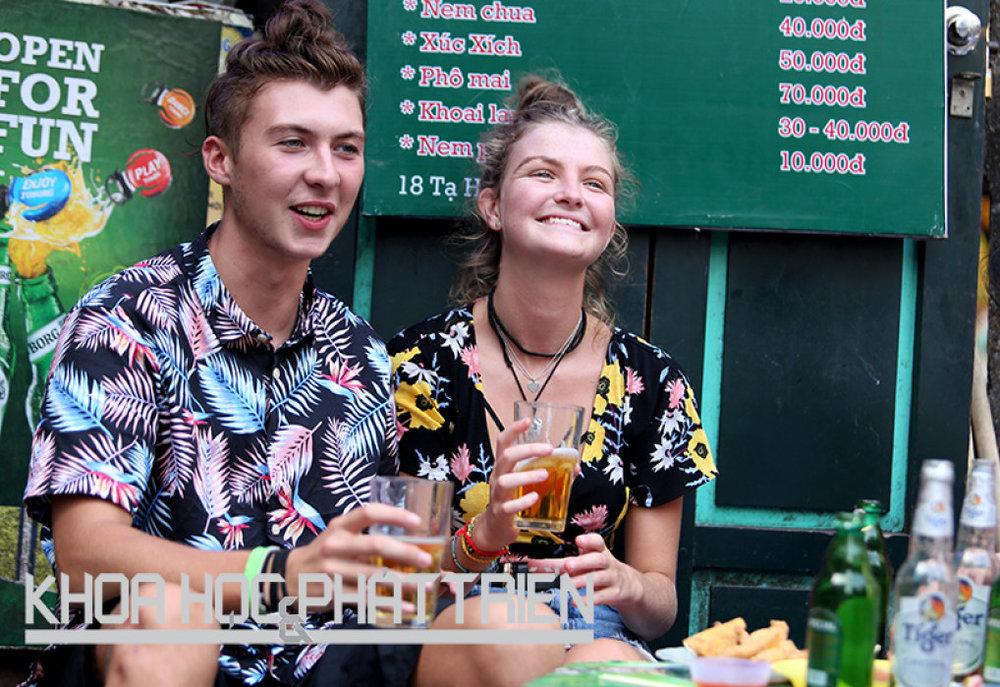 """Hai du khách người Anh đang thưởng thức """"bia hơi vỉa hè"""" trên phố Tạ Hiện, Hà Nội. Ảnh: Loan Lê"""