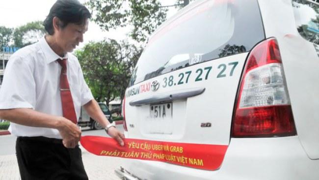 Tài xế gỡ yêu cầu dán đằng sau xe taxi. Ảnh: Cao Thăng