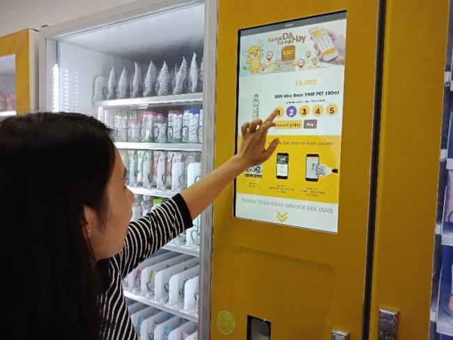 Có các màn hình cảm ứng hiển thị toàn bộ hàng hóa và giá bán ở mỗi máy bán hàng. Người dùng chỉ việc chọn vào món mình muốn mua, sau đó chọn số lượng cần mua.