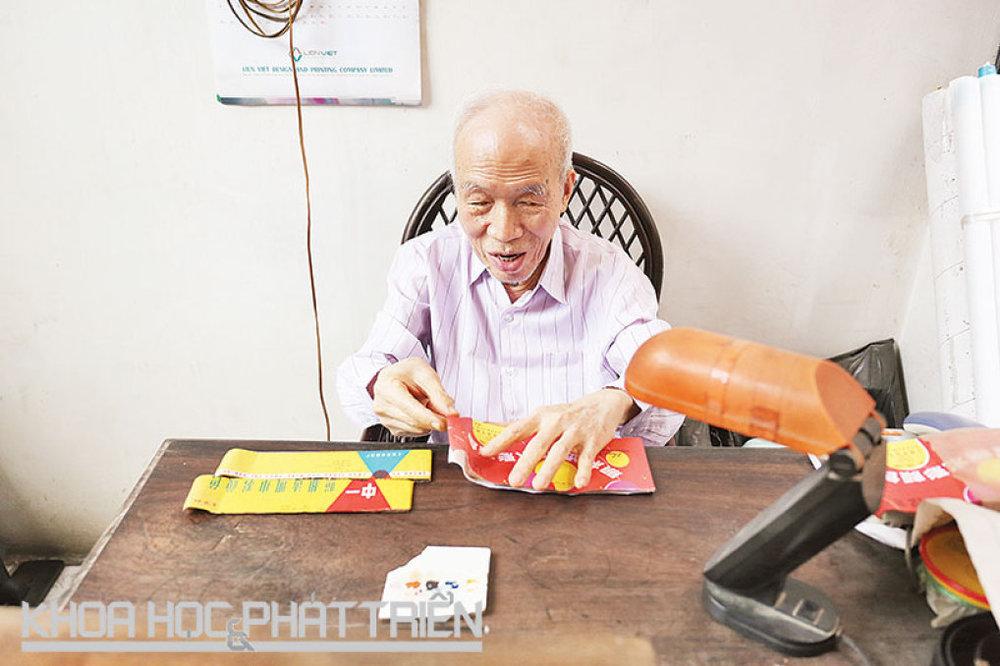 Nghệ nhân Phạm Đăng Hưng ngồi trên chiếc bàn nơi ông đã chỉnh sửa hàng nghìn bức ảnh.