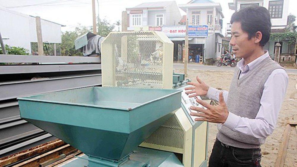 Anh Trần Đình Lai bên chiếc máy ép củi trấu do anh sáng chế
