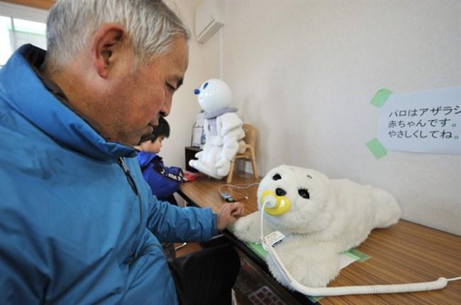Robot Paro (phải) mang đến niềm vui cho người cao tuổi tại Kesennuma, tỉnh Miyagi, Nhật Bản