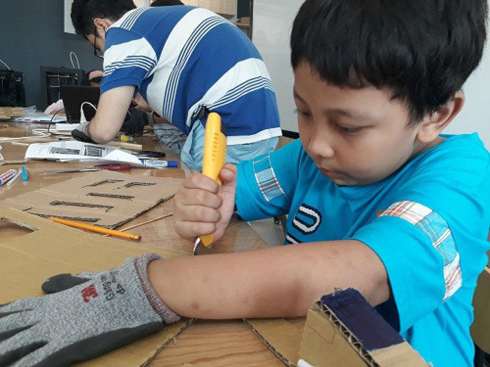 Em Đặng Hoàng Minh Nhật, học sinh lớp 3 đang tỉ mỉ cắt những tấm bìa cac tông để tạo hình cho sản phẩm của mình. Ảnh: Hà Thế An.