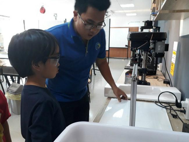 Các em học sinh khi thao tác với máy móc đều phải mang găng tay và kính bảo vệ. Ảnh: Hà Thế An.