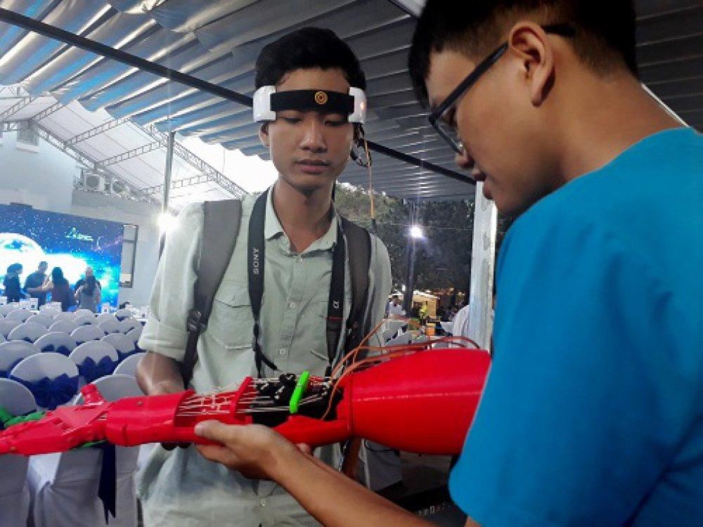 Lê Mạnh Trường, sinh viên ĐH Bách khoa TP.HCM (phải) hướng dẫn cho một khách quan tâm về thiết bị điều khiển cánh tay giả bằng sóng não. Ảnh: Hà Thế An.