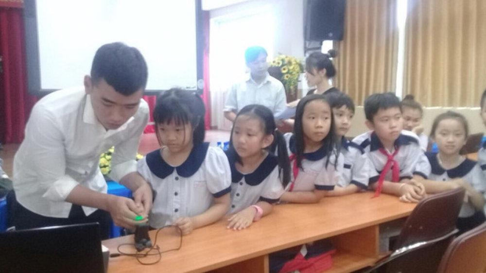 Nhân viên Trung tâm quản lý giao thông công cộng TP.HCM lấy vân tay của học sinh Trường tiểu học Nguyễn Bỉnh Khiêm  . Ảnh: Bảo Châu