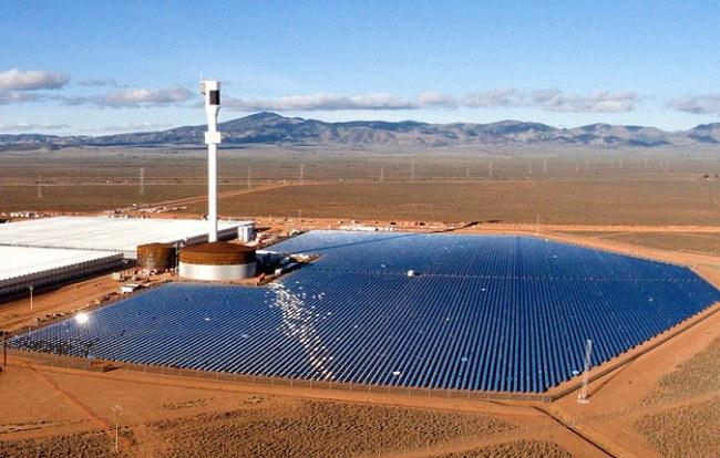 Toàn cảnh Sundrop Farms với bốn khu nhà kính một bên và hệ thống kính hội tụ ánh nắng mặt trời một bên, ở giữa là ngọn tháp cao 127 m với nồi hơi nước năng lượng.