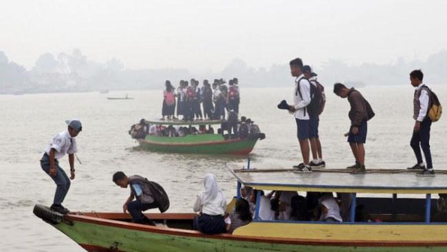 Học sinh qua sông Ogan đi đến trường trong bầu không khí mù khói từ các vụ cháy rừng ở Inhonesia - Ảnh: Reuters