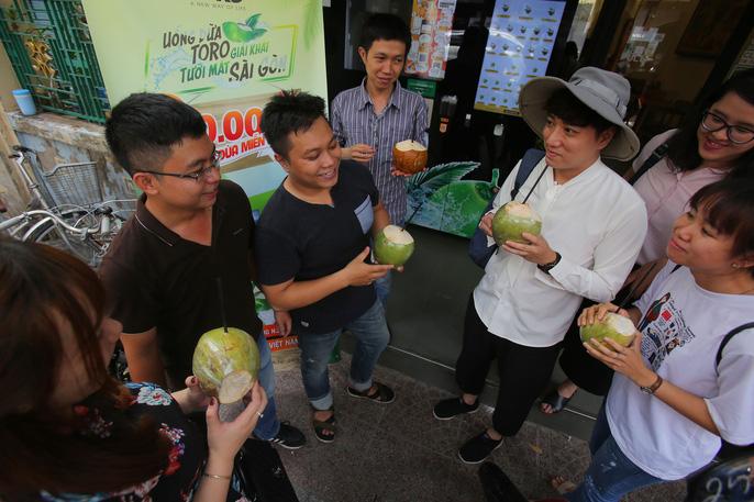 Các bạn trẻ thích thú giải nhiệt với những trái dừa được tặng miễn phí từ máy bán dừa tự động trên đường Hồ Tùng Mậu, quận 1