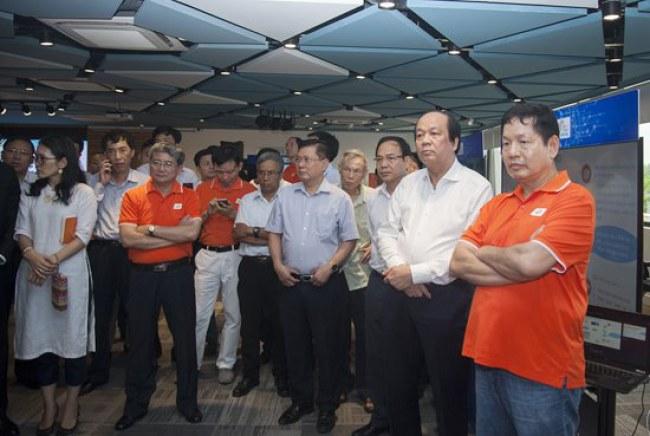 Bộ trưởng Chủ nhiệm Văn phòng Chính phủ Mai Tiến Dũng và các thành viên trong đoàn công tác nghe chia sẻ giải pháp Chính quyền điện tử tại Quảng Ninh (Ảnh FPT cung cấp)