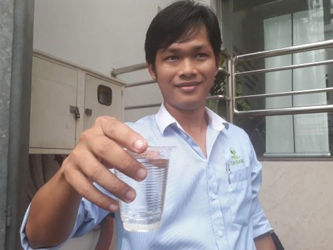 Th.s Ngô Quang Hiếu cầm trên tay ly nước thải ra môi trường sau khi qua xử lý tại Viện gút TP.HCM. Ảnh: Hà Thế An.