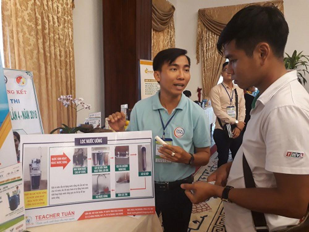 Thầy giáo trẻ Hồ Văn Tuấn (trái) giới thiệu sản phẩm cho một khách tham quan về hệ thống xử lý nước của mình sáng chế. Ảnh: Hà Thế An.