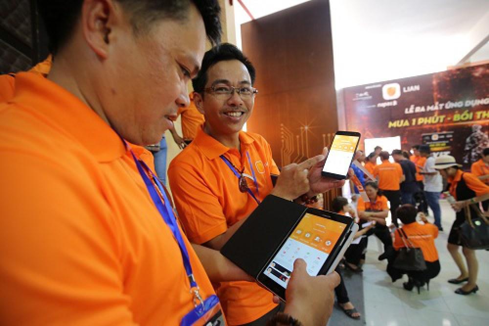 Người dân trải nghiệm bảo hiểm điện tử trên điện thoại và máy tính bảng  tại lễ ra mắt ứng dụng bảo hiểm điện tử đầu tiên tại Việt Nam. Ảnh: BTC.