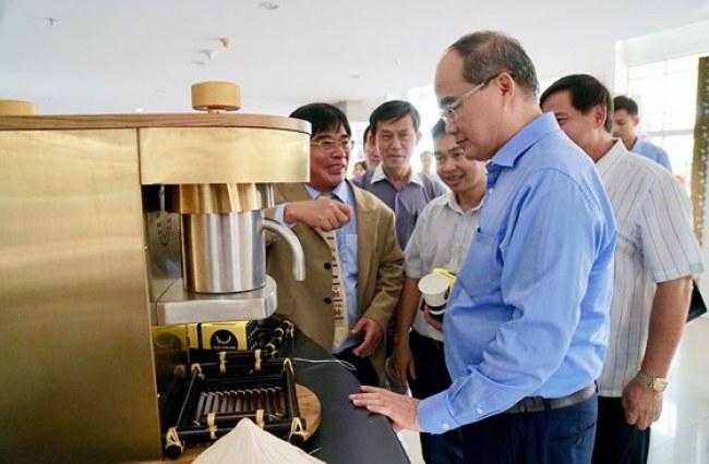 Bí thư Thành ủy TPHCM Nguyễn Thiện Nhân xem máy pha cà phê tự động. Ảnh: HOÀNG HÙNG