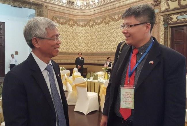 Giáo sư Trần Hải Linh trao đổi với ông Võ Văn Hoan, Chánh Văn phòng UBND TP.HCM bên lề hội nghị. Ảnh: TÁ LÂM