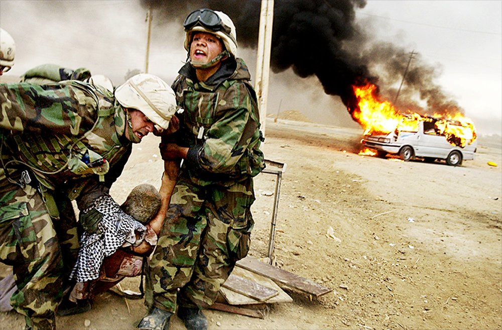 Risking their lives to save another, Lt. Jeffery Goodman and Lance Cpl. Jorge Sanchez of the 2nd Tank Battalion drag a wounded civilian to safety after he was caught in the midst of battle on the road to Baghdad, Iraq, on April 4, 2003.