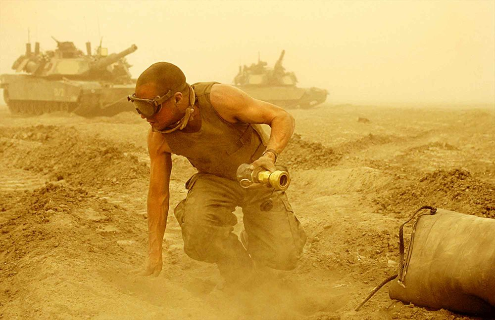 Marine Staff Sgt. Brian Flaherty of New York, Delta Company of the 2nd Tank Battalion, disconnects a fuel bladder from a tank as a dust storm rages in preparation for an advance to the north of Iraq on March 25, 2003.  The Marine's move north has been one of the most aggressive tank road marches in history.
