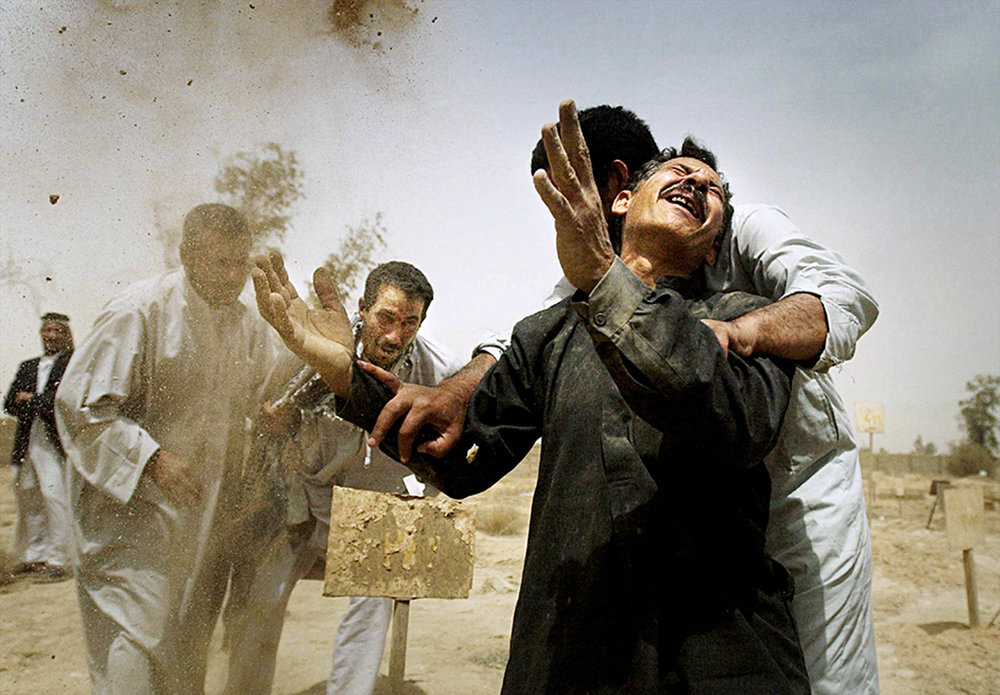 Overcome with emotion after the remains of their brothers were unearthed at a mass grave in Abu Ghraib Cemetery, Ali Majeed Al Shumary leans on Mohammad Bakar Whathiq as the men grieve in Baghdad, Iraq, on April 25, 2003. Their brothers Walid Majeed Al Shumary and Brer Bakar Whathiq were killed for opposing President Saddam Hussein's regime.