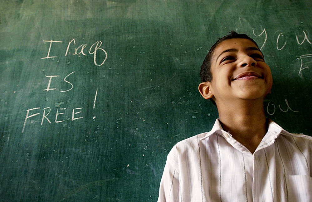 Uniss Mohammad Salman, 10, returns to Al Amtithal Elementary School to a message on the chalkboard from U.S. soldiers--Iraq is free!  Al Amtithal was the first school to reopen in Baghdad, Iraq, on April 27, 2003. Of 1200 pupils, only a handful of children returned. Short informal lessons were conducted, but mostly children familiarized themselves with their surroundings.