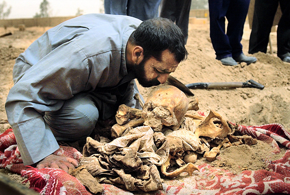 At Baghdad's Abu Ghraib Cemetery, Mohammad Bakar Whathiq lovingly kisses the skull of his brother, Brer Bakar Whathiq, who was killed in 1993 for opposing Saddam Hussein's regime, in Iraq, on April 25, 2003.