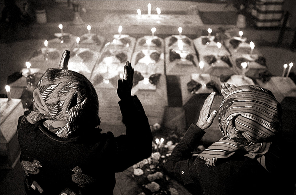 Mayan priests Domingo Morales and Cristobal Velasquez perform a traditional Mayan ritual to calm the spirits of 23 massacre victims in Chupol. Only three families came to claim their relative's bones and participate in traditional ceremonies for the deceased, as fear is still rampant in the Guatemalan countryside where thousands were brutally killed during the country's 36-year civil war.