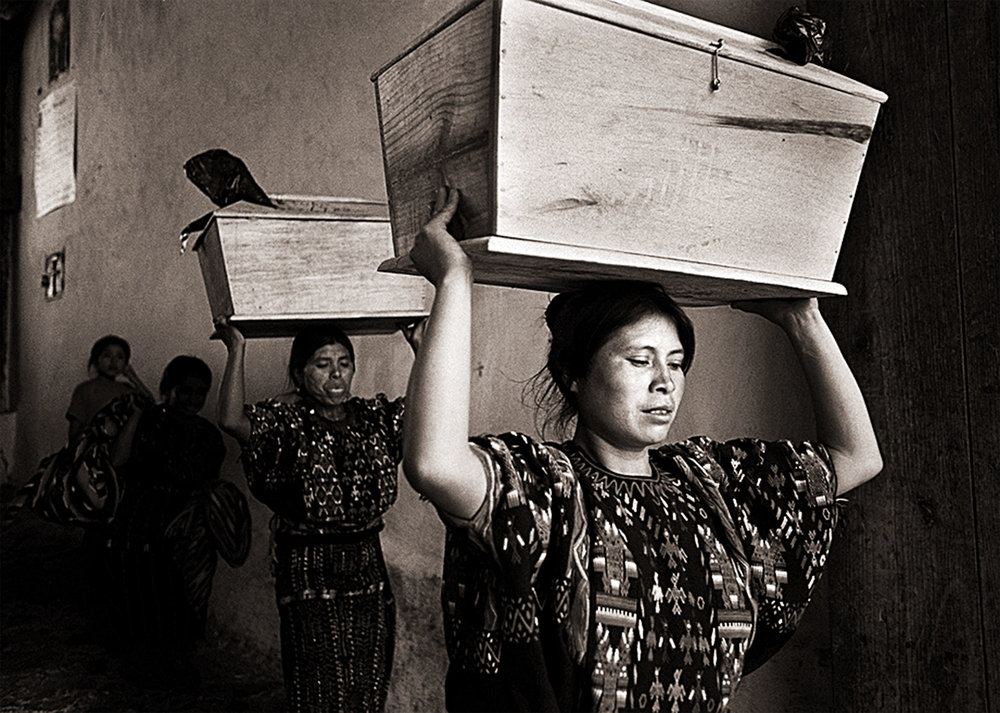Widows Isabella Mejia and Maria Macari tread carefully as they depart the Iglesia Catolica de Chichicastenango carrying the bones of their late husbands home to their village of Chupol, Guatemala. Mejia and Macari's husbands were massacred during the country's civil war.