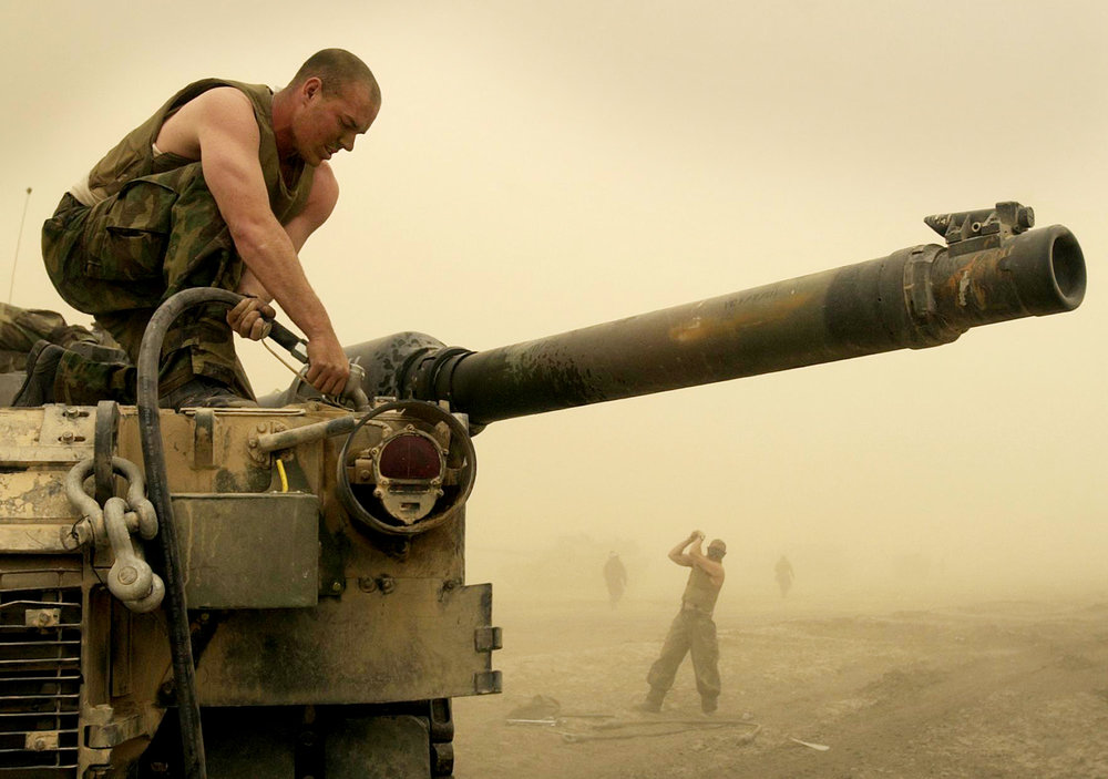 Marine Sergeant Louis DeMarco of New York's Delta Company of the Second Tank Battalion, fuels a tank as a dust storm rages in preparation for an advance on Baghdad, Iraq, on March 23, 2003. The move north has been one of the longest and most aggressive tank road marches in Marine history.
