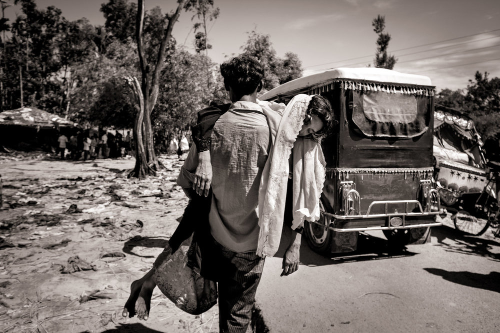 Hungry, tired and dehydrated, a Rohingya refugee carries his unconscious wife to a nearby auto rickshaw as they flee to Bangladesh, in Teknaf Upazila, on Oct. 4, 2017. Many refugees spoke of drinking salt water for several days to survive and fights erupting as they waited for boats to ferry them from Myanmar to Bangladesh.