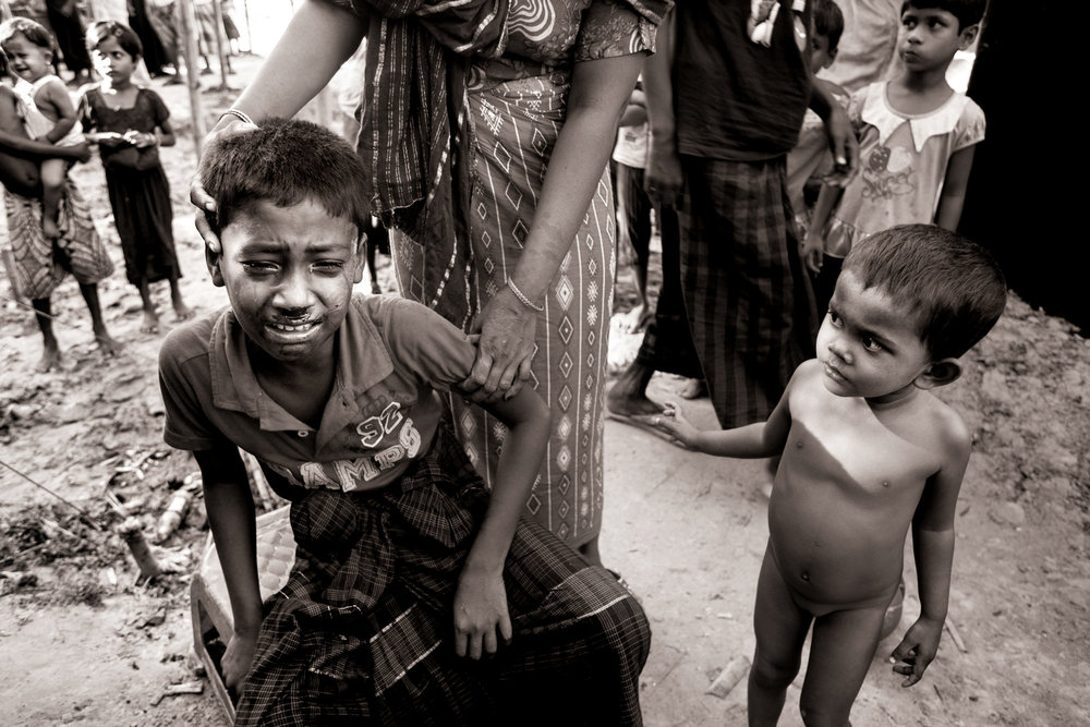 Orphan Mohammadshakir Mohammadkaisar, 10, is comforted by his aunt Yasmin Nurulhaq while cousin Zeshmintara Nurulhaq, 4, watches, after the boy was hit in the face during an altercation in Zadimora village near the Myanmar border in Bangladesh, Oct. 10, 2017. Tensions among refugees escalate as the stress of hunger, poverty and the ongoing violence in their home country flares. The unregistered refugee camp is growing with plastic, tarpaulin and bamboo shelters built by newly-arrived Rohingya refugees. Water and sanitation is severely lacking in unregistered camps where NGOs are unable to support them, raising the risk for water-born disease, dysentery and cholera.