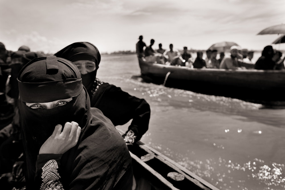 Myanmar's Rohingya refugee Anwara Nurhassan, right, takes a boat from Chalpuridip, Bangladesh, as she continues her journey to refugee camps further in the country on Oct. 3, 2017.
