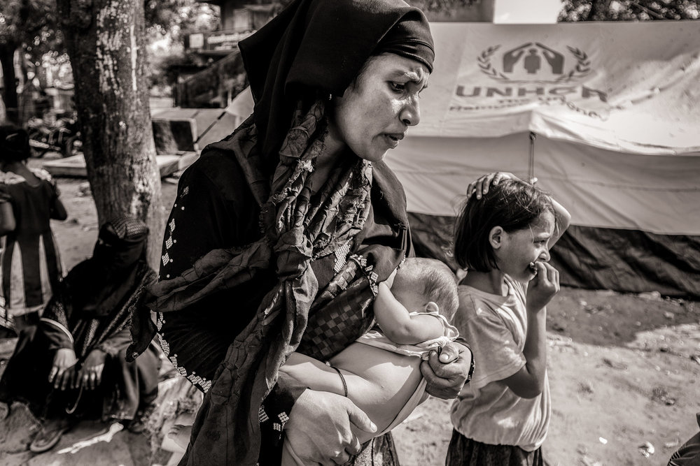 Rohingya refugee Morean Katu nurses her six-month-old daughter Tokhia Katu while waiting with daughter Sherfara Katu, age 11, at an army post in Teknaf Upazila, after escaping from Myanmar into Bangladesh on Oct. 2, 2017. She and over 1000 refugees eventually loaded onto trucks with provisions provided by non-governmental organizations as they made their way to refugee camps.