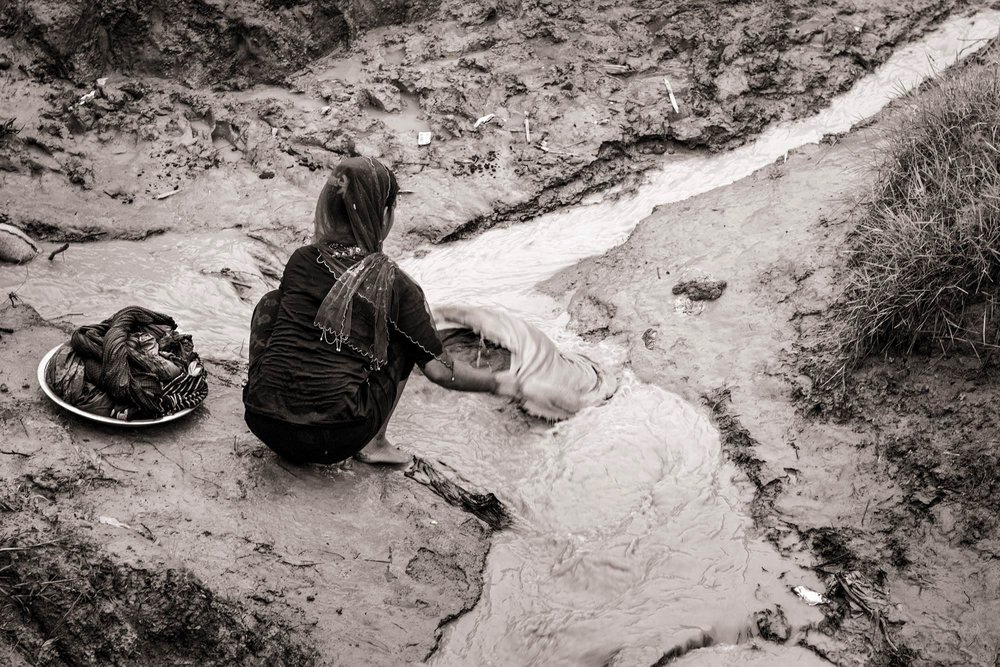 """Dilkayas Salehahmad, 11, washes clothes in the muddy waters flowing through Whaikhyang Refugee Camp in Bangladesh on Oct. 6, 2017. Only a month earlier, Dilkayas and her parents fled their village of Khawerbil Moungdaw in Myanmar to come to Bangladesh. Her father is blind after an attack by Buddhists in 2012. """"We don't have any water in our shelter so I wash clothes in the stream,"""" said Dilkayas."""